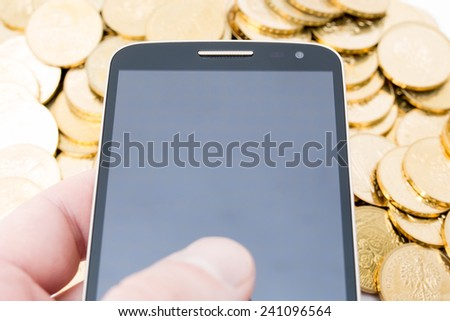 Cellphone with golden coins - stock photo