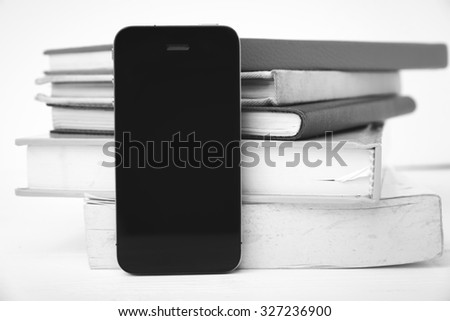 cellphone with stack of book over white table black and white tone color style