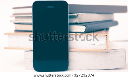 cellphone with stack of book over white table vintage style