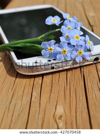 Cellphone with tiny blue flowers (forget-me-not) on a wooden board. Space for text. - stock photo