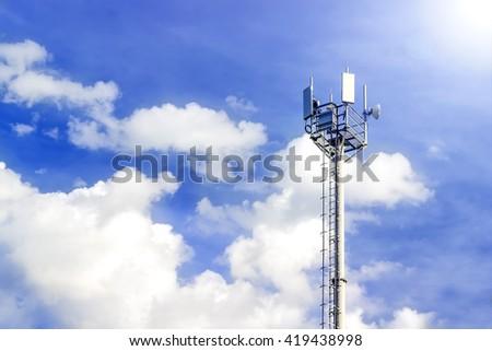 Cellular antenna against blue sky - stock photo
