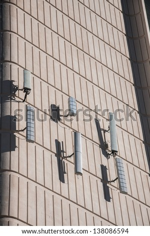 Cellular antenna mounted to the wall of building. - stock photo
