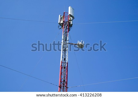 Cellular communications tower on a background blue summer sky . GSM antenna - stock photo