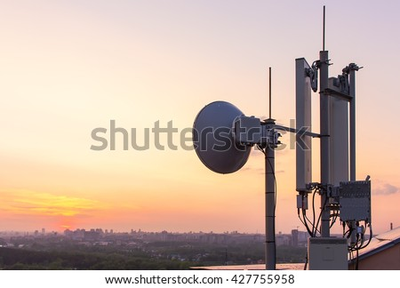 cellular communications tower on a background of the city and a beautiful sunset in summer - stock photo