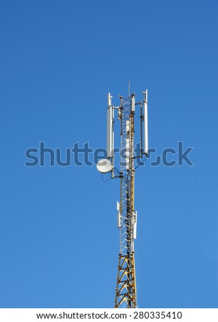 Cellular transmitter on blue sky background - stock photo