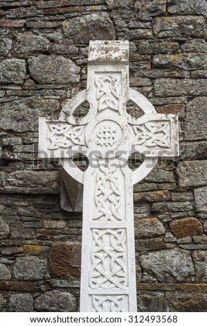 Celtic cross gravestone against ancient stone wall background - stock photo