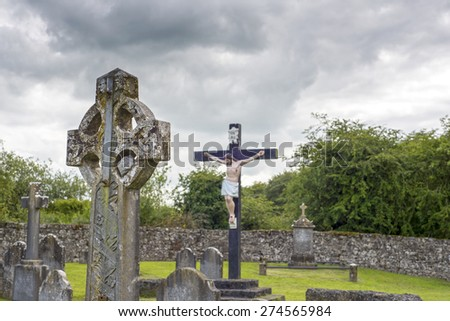 celtic cross headstone and crucifix in a graveyard in county tipperary ireland - stock photo
