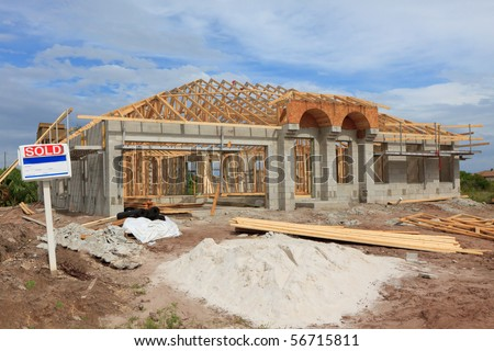 Cement Block home under construction, wood trusses installed. Sold sign in front - stock photo