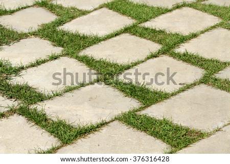 Cement block pathway on field - stock photo