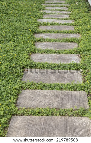 cement brick walkway on green grass background - stock photo