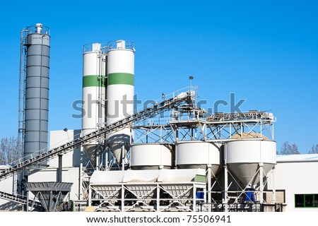 Cement factory machinery on a clear blue day - stock photo