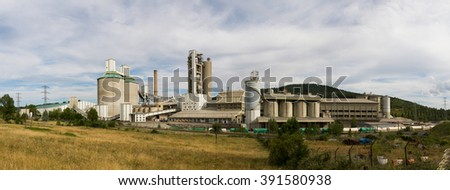 Cement Manufacturing Plant -  Panoramic view of industrial plant for the manufacture of cement with warehouses, silos and towers