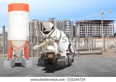Cement mixer truck parked in front of a new building under construction with precast concrete piles - stock photo