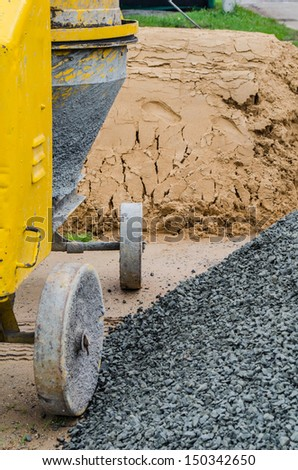 Cement mixer with sand and gravel mixing trough at a building site. - stock photo