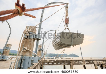 cement port pier jetty and wood boat hanging on the Davits - stock photo