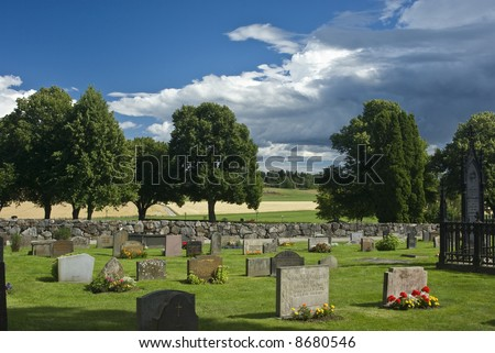 cemetery in summer with storm on horizon - stock photo