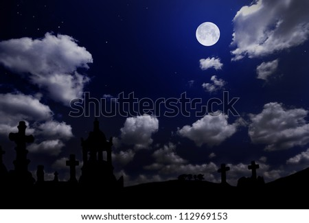 Cemetery under night cloudy sky with moon