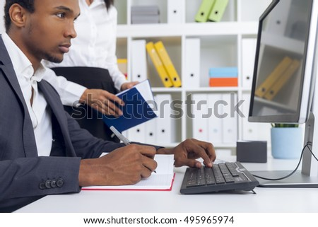 Centered African American guy is looking at computer screen and typing. His colleague is standing beside him