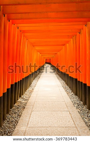 Centered stone walkway leads straight down the middle of repeating symmetrical red torii gates at Fushimi Inari Shrine during daytime with nobody present in Kyoto, Japan. Vertical copy space