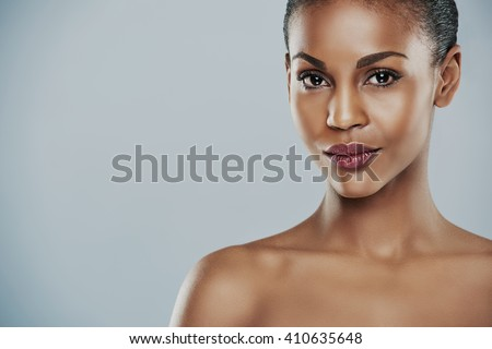 Centered view of beautiful grinning African bare shouldered female with short hair and seductive expression and over gray background - stock photo