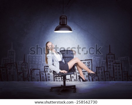 Centered woman wearing jacket and blouse sitting with legs crossed. Background sketch of buildings - stock photo