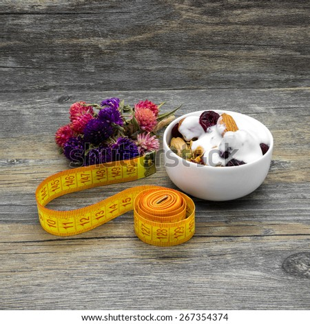 Centimeter and granola with yogurt on rustic wooden background. - stock photo
