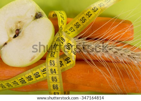 centimeter, carrots and an apple on a green background;