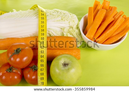 centimeter, fresh carrots, apples, cabbage and tomatoes on a green background