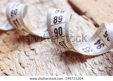 Centimeter on the table. Measuring tape on a table. Diet, weight loss, sports. The concept of slimness. Wellness. Measuring tape on old wooden table.  - stock photo