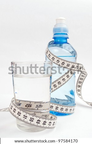 Centimeter tape wrapped around glass and bottle of water on the white background