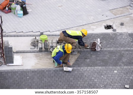 CENTRAL BANGKOK THAILAND ASIA - CIRCA 2014 - Asian workmen laying block paving to form a sidewalk in the city centre