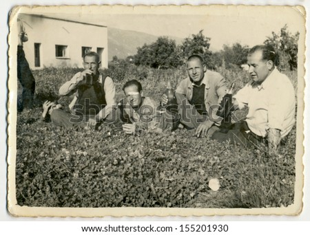 CENTRAL BULGARIA, BULGARIA - CIRCA 1955: A group of men drinking alcohol (raki or wine) in the meadow in front of a small white house - Note: slight blurriness, better at smaller sizes - circa 1955