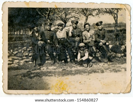 CENTRAL BULGARIA, BULGARIA - CIRCA 1945: A group of men in civilian clothes and soldiers sitting on a stone wall - Note: slight blurriness, better at smaller sizes - circa 1945