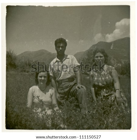 CENTRAL BULGARIA, BULGARIA,- CIRCA 1950: photo is a body, in the Rhodope Mountains, the area Karlovo - two young women and man on the meadow - circa 1950