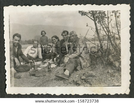 CENTRAL BULGARIA, BULGARIA- CIRCA 1955: the area Plovdiv- A group of people (mostly men) sitting on blankets on the field and drinking wine- Note: slight blurriness, better at smaller sizes-circa 1955