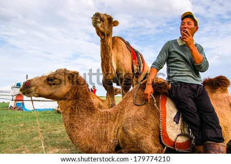 CENTRAL MONGOLIA - JULY 27, 2010: Cameleer relaxing with his camels in front of a yurt (known in Mongolia as a ger) on the steppe of central Mongolia - stock photo