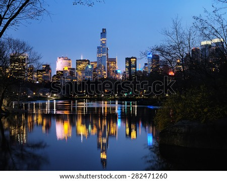Central Park in dusk buildings reflection in midtown Manhattan New York City  - stock photo