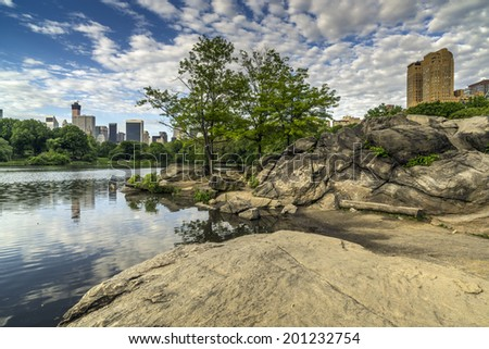 Central Park, New York City by the lake in the early morning with heavy clouds - stock photo
