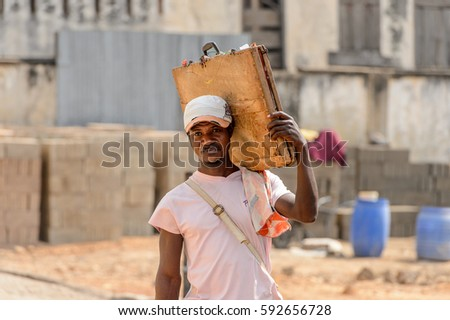 CENTRAL REGION, GHANA - Jan 17, 2017: Unidentified Ghanaian man carries an old case on his shoulder in local village. People of Ghana suffer of poverty due to the bad economy