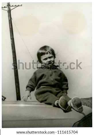 Central Slovakia, CZECHOSLOVAK REPUBLIC, CIRCA 1975 - baby sitting on the front hood of the car - circa 1975 - stock photo