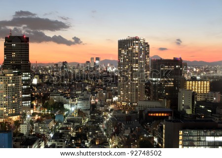 Central Tokyo lights turning on during sunset with Mount Fuji in the background - stock photo