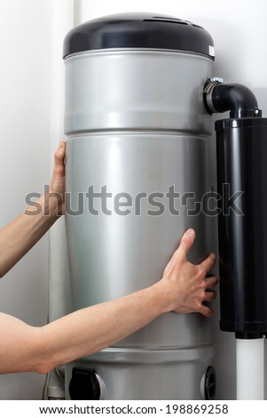 Central vacuum cleaner installation, handyman at work - stock photo