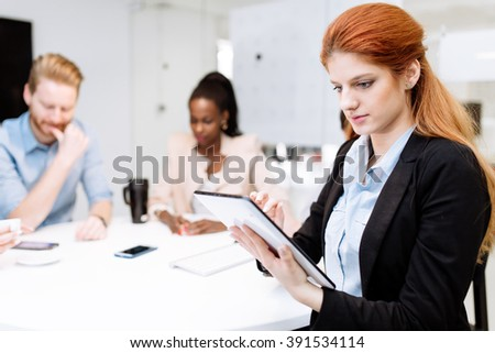 CEO of company holding tablet at team board meeting