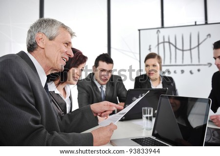 CEO reading report at business meeting - stock photo