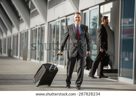 CEO travels light with small carry on bag at the airport - stock photo