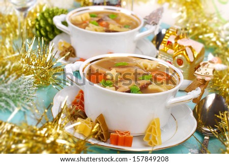 cep soup with star or christmas tree`s shape pasta on festive table - stock photo