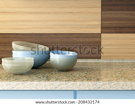 Ceramic and glass kitchenware on the marble worktop in front of modern wooden wall. - stock photo