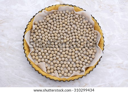 Ceramic beans used as pastry weights in an uncooked pie crust lined with greaseproof paper - stock photo