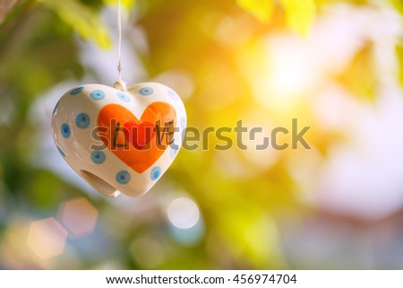 Ceramic bell heart shaped and word Love with green nature background - stock photo