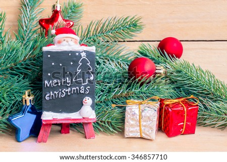 Ceramic black board with christmas tree twigs of spruce and christmas decoration on a wood table